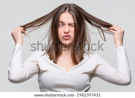 Messy hair. Brunette woman with messed hairs. Girl having a bad hair. Bad hairs day. Frustrated woman having a bad hair. Woman having a bad hairs, her hair is messy and tangled.