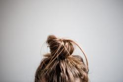 Messy hair bun closeup with grey white background.