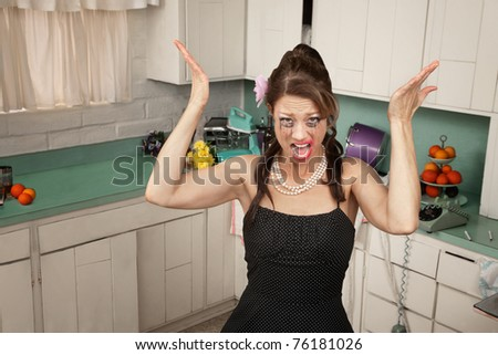 Messy housewife in kitchen yells with her hands raised