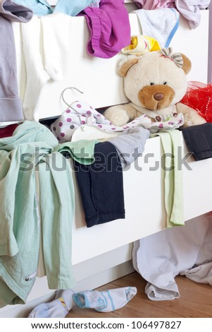 Messy kids room with clothes in drawer
