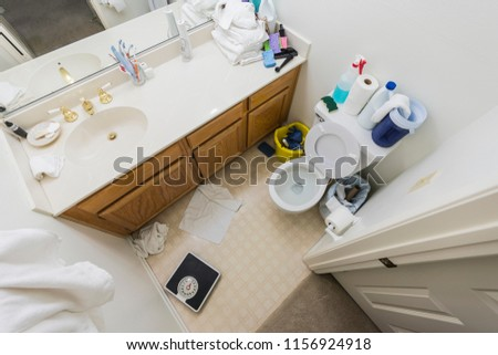 Messy little half bathroom with dirty towels and cleaning clutter.