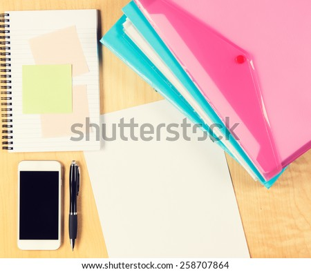 Messy office table with smartphone, notepad and filling folders. View from above with copy space