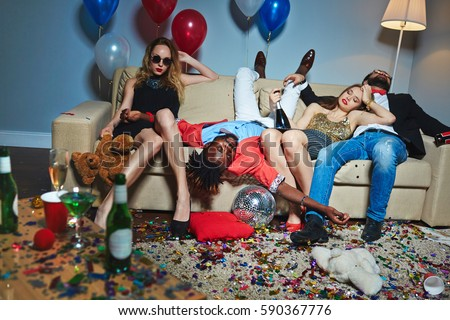 Messy room after wild house party, three tipsy stylish friends relaxing on couch while blond-haired woman with teddy bear posing for photography #590367776