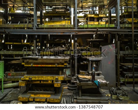 messy stamping shop with large stamps rack inside metalworking factory #1387548707