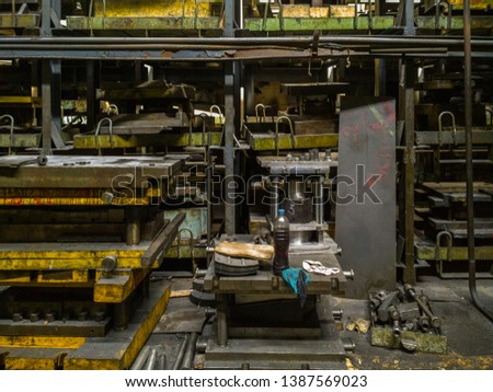 messy stamping shop with large stamps rack inside metalworking factory #1387569023
