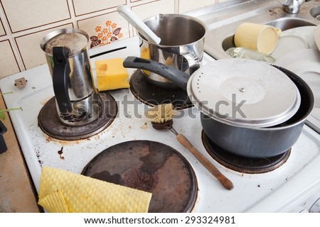 messy stove in domestic kitchen with grungy dishware, old pot and espresso maker, with dirty and used scrubber and yellow sponge