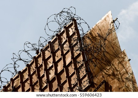 Messy tangled barbed spiked wire on wall fence roof of shophouses along streets of South East Asia city Singapore Malaysia #559606423