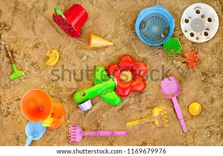 Messy toys in sand on playpit. Top view. Playthings in sand-pit, overhead shot. Sandbox with baubles. Moulding sand quarry with colorful gimcrackery. Knick-knackery in gravel. Sundry nugae in greva.