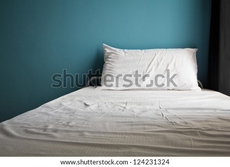 Messy white bed and one pillow , light blue wall in the morning