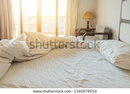 Messy white bedding sheet and white pillow after waking up in the morning with sunshine shining through window with curtains in to the bed room, waking up concept #1560678056