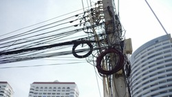 Messy wires attached to the electric pole, the chaos of cables and wires on an electric pole Thailand, concept of electricity