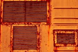 Metal air grilles. An old rusty sheet of metal. The texture of sheet metal, the grunge style. An empty orange background.