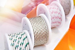 Metal and fabric braided cables on spools in electronic store
