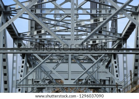Metal and steel bars, beams and structures of the bridge against blue sky #1296037090
