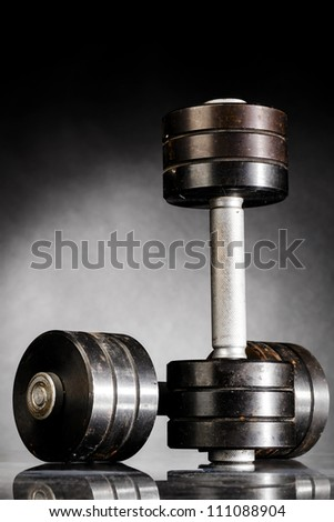 metal barbells on dark gray background