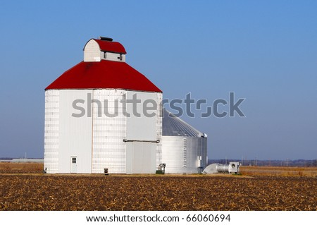 Metal barn silo in a field with blue sky and and copy space