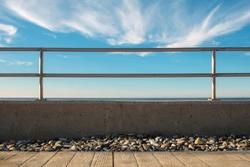 Metal barrier or railings between promenade and blue sea