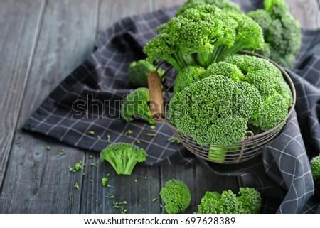 Metal basket with fresh green broccoli and napkin on table