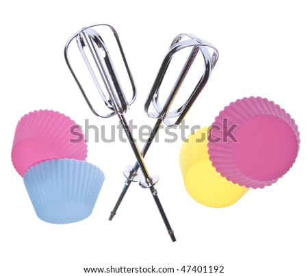 Metal beaters and cupcake tins in a fun pose for a cupcake party.  Isolated on white with a clipping path. - stock photo