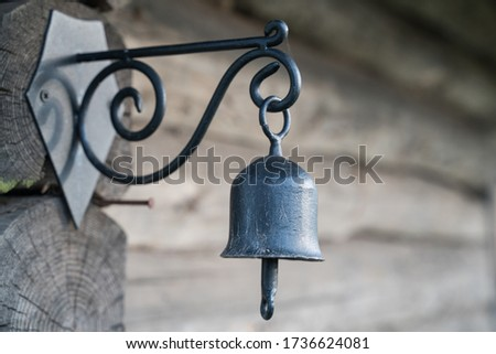 Metal bell attached to the timber wall. Log cabin wall and smith manufactured bell attached to it. Nice looking steel bell on the wall. Dark steel bell. Focus on the bells, background blurred.