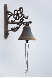 Metal bell hanging on white wall