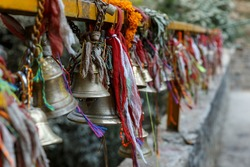 metal bells hang on chains in a Hindu temple. Dakshinkali Temple in Pharping, Nepal.
