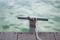 Metal boat cleat on dock on lake with white rope during day in summer