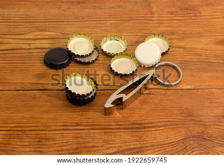 Metal bottle opener in the form of a keychain with attached steel split ring and different used metal crown bottle caps on an old rustic table ストックフォト ©