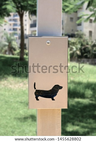 Metal boxes with free bags for collect dogs owners dog excrement. These boxes are set by the city municipality in public parks and public gardens for hygiene and cleanliness #1455628802
