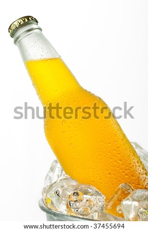 Metal bucket full with ice and a glass bottle of orange beverage