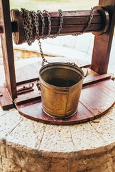 Metal bucket with chain on a vintage authentic well - ancient underground water pipe