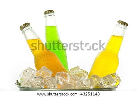 Metal bucket with ice cubes with cold glass bottles of colorful drink