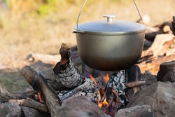 Metal cauldron boiling on a bonfire. Cooking on open fire, camping meal