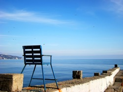 Metal chair on the pier, against the backdrop of a calm sea and blue sky