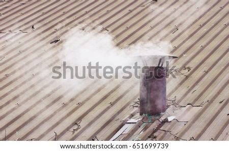 Metal chimney on copper roof with smoke - image with copy space #651699739