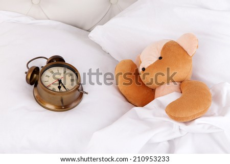Metal clock and toy bear on pillows on a big white bed