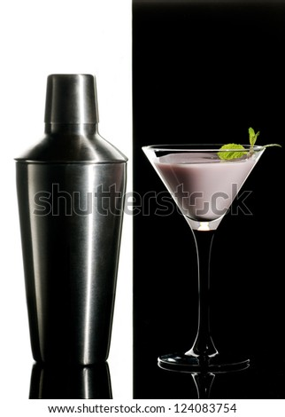 Metal cocktail shaker and cream cocktail with mint leaves on a black and white  background
