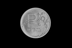 Metal coin of one russian rouble on black background.