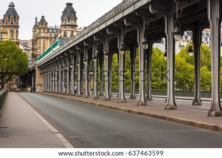 Metal columns and abutments of '' Bir Hakeim '' bridge. People walks and make jogging under the bridge in Paris.The bridge is one of the most famous and historic landmark #637463599