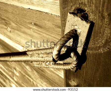Metal construction close down the door, background old wood wall