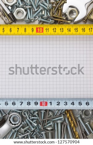 metal construction  hardware tool on checked paper