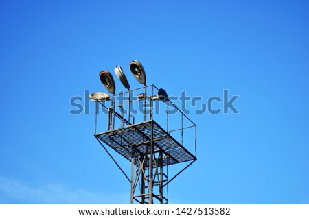 Metal construction with a ladder leading into the sky. Large illuminator with lamps and lanterns. Old abandoned lamppost - Image #1427513582