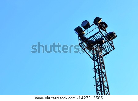 Metal construction with a ladder leading into the sky. Large illuminator with lamps and lanterns. Old abandoned lamppost - Image #1427513585