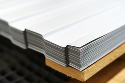 Metal corrugated board. A stack of roofing sheets is in the store's warehouse. Close-up. Copy space