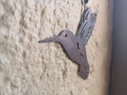 metal cut-out hummingbird decoration against a wall
