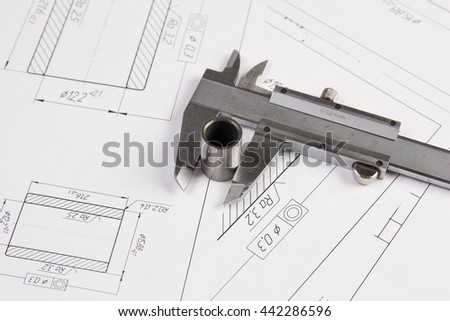 Metal cylinders and calipers on printed engineering drawings. Mechanics and Engineering Technology. Engineering drawings of steel parts.