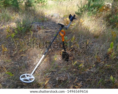 metal detector with a shovel stands in dry grass and vegetation in the forest