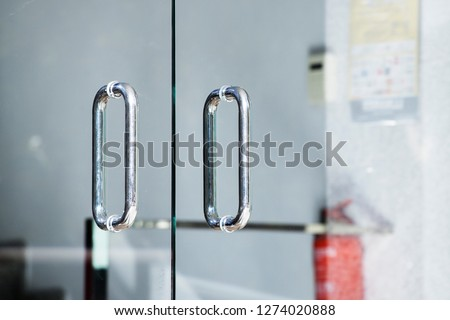 Metal door handle. Door handle on the glass door. Glass doors. Style. Modern interior. Entrance. Office. Office building.
