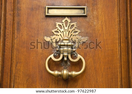 Metal door handle knocker on a wooden door
