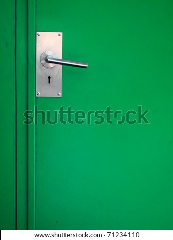 Metal door handle on green steel door